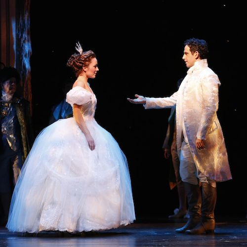 On stage during a Broadway production, an actor portraying Prince Charming extends his hand to Cinderella for a dance at the ball.