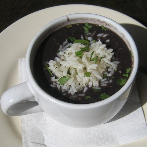 A white ceramic mug filled with black bean soup, garnished with white rice.