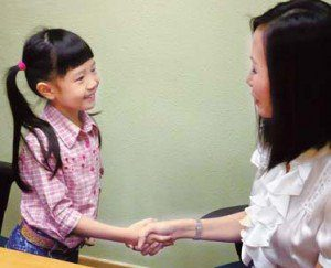 A young girl smiles and shakes hands with an adult woman.
