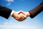 Stock image of a handshake against a blue sky.