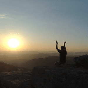 A man meditating towards the sun on a mountaintop.