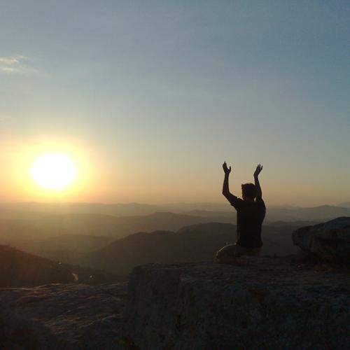 A man meditating towards the sun on a mountaintop.