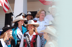 Shareholder Jody Stahancyk laughs along with a group of rodeo attendees on the porch of the Prineville office of Stahancyk, Kent and Hook.