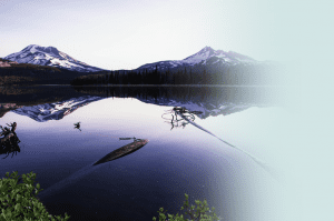 A reflective lake with two mountains in the distance.