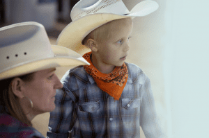 A woman kneels next to a boy at a rodeo, both in cowboy garb.