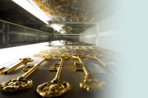A closeup of golden keys kept under a glass enclosure.
