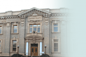 A medium shot of the Clatsop County Courthouse in Astoria, Oregon - a two story building with a light-tan brick facade.