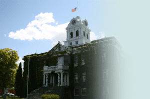 A medium shot of the Crook County Courthouse - a two story building with climbing vines.
