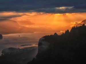 The sun sets on the Columbia river in an impressive array of golden orange colors.