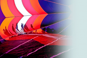 The shadows of onlookers appear against the backdrop of a billowing, grounded hot air balloon.