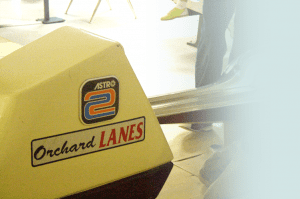 "A closeup of a ball return at a ""Orchard Lanes"" bowling alley."