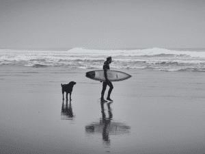 Man walks on beach with Dog holding a surfboard.