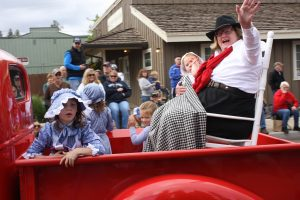 Jody Stahancyk Grand Marshal of the Crooked River Roundup 2017 waving from an old red truck